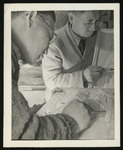 [Two adult males sketching/wood carving]