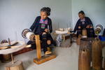 Wu Huazhuan and Wu Yingniang spinning thread on large cones by Marie Anna Lee