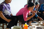 Wu Mnci eating lunch with helpers by Marie Anna Lee