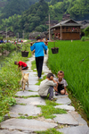 Woman, dog and children near the river during volunteer firefighter competition by Marie Anna Lee