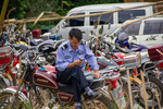 An Official on motorbike with phone by Marie Anna Lee