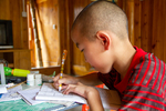 Child doing homework by Marie Anna Lee
