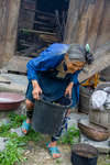 Wu Meitz carrying a bucket with mulberry bark by Marie Anna Lee