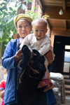 Woman demonstrates infant carrier use by Marie Anna Lee
