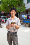 Man holding a bird in Liping by Marie Anna Lee