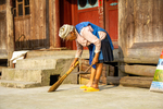 Woman sweeping rice grains by Marie Anna Lee