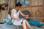 Woman weaving flower belt by Marie Anna Lee