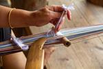 Wu Liangming weaving a flower belt on backstrap loom by Marie Anna Lee