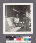 One man #33 [seated with magazine on porch] by Richard Shizuo Yoshikawa