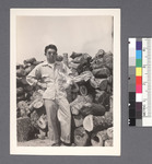 One man #35 [in front of woodpile; hands on hips] by Richard Shizuo Yoshikawa